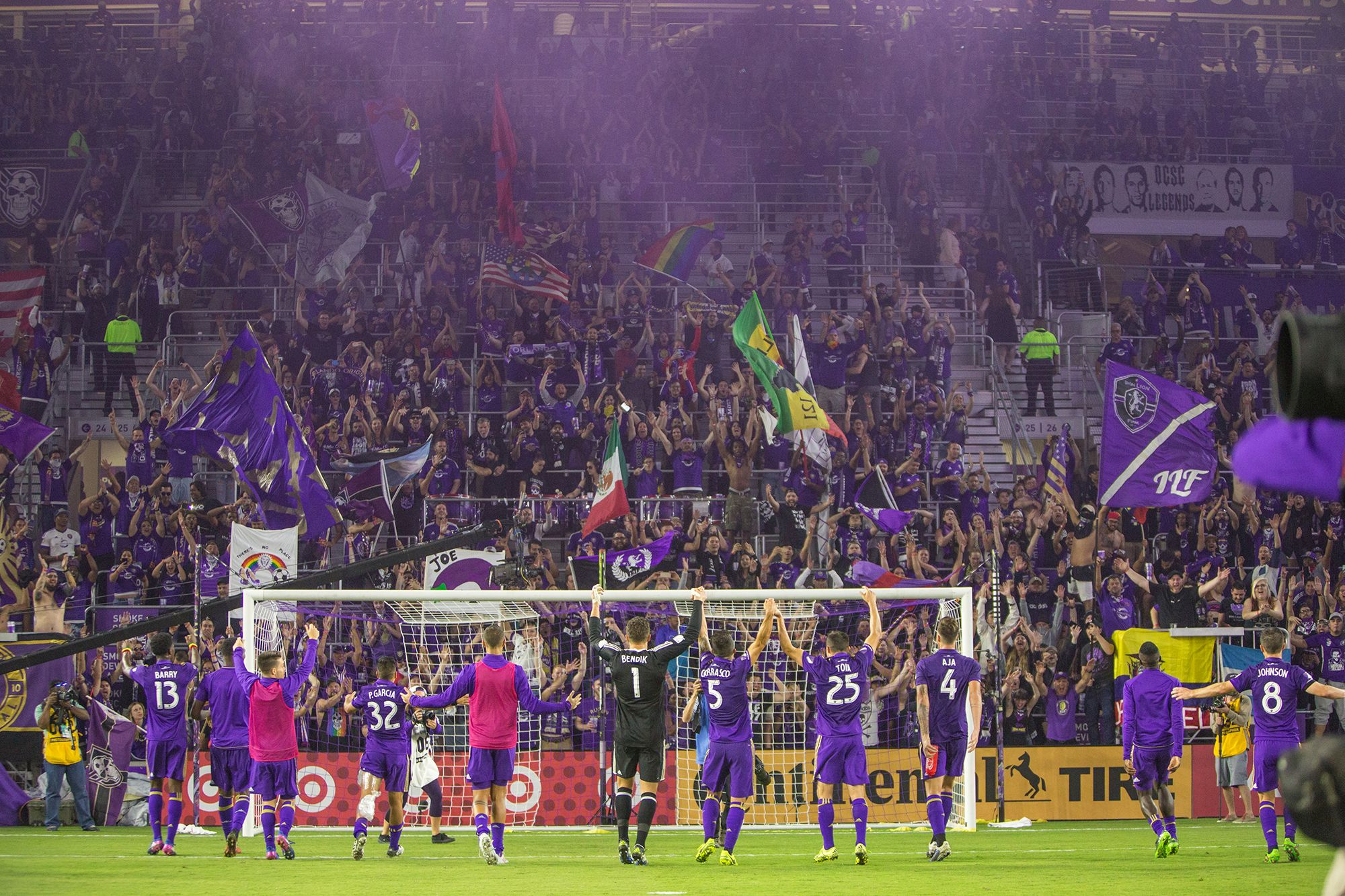 Orlando City players celebrate with supporters after a match.