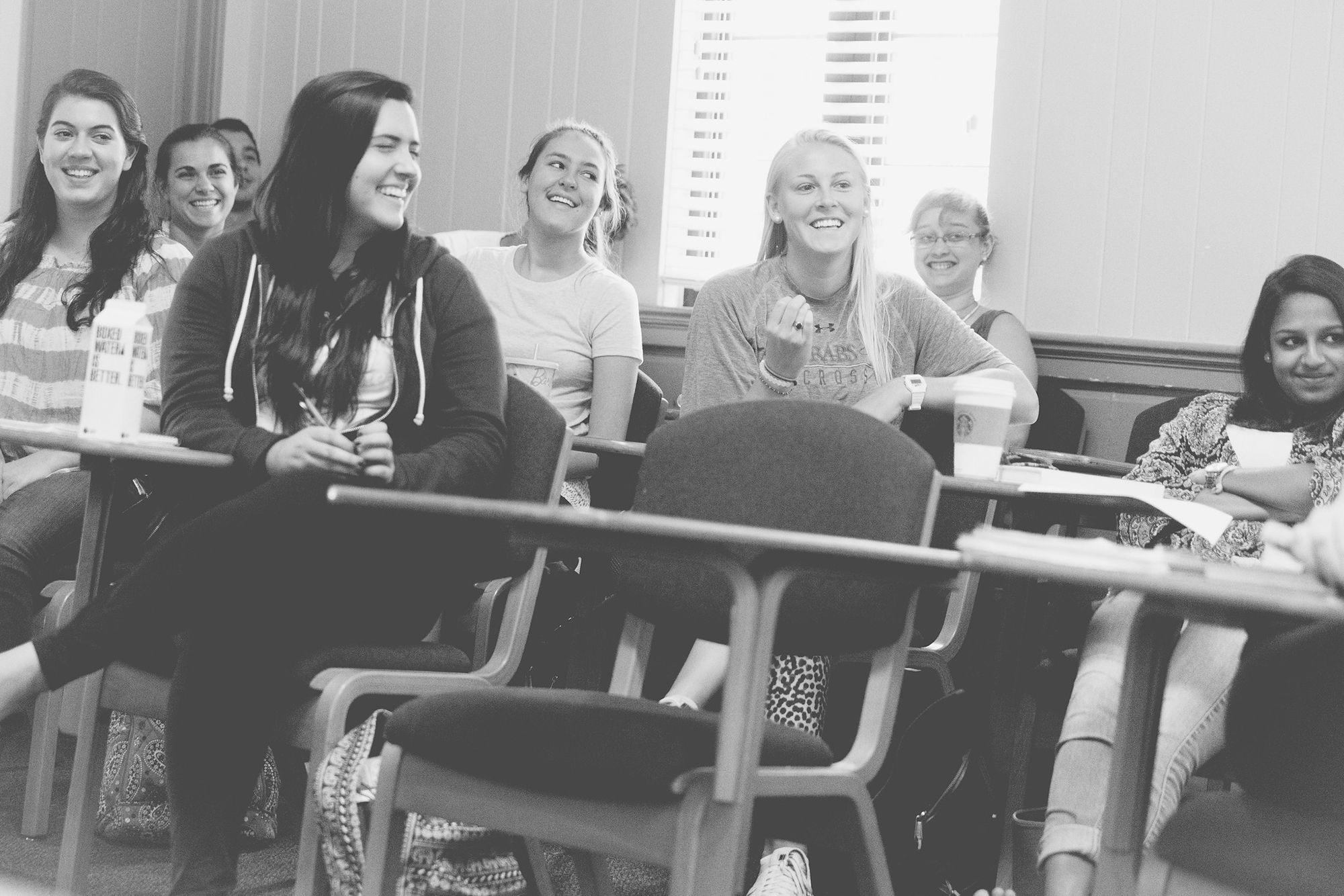 Philosophy students sitting in desks smiling.