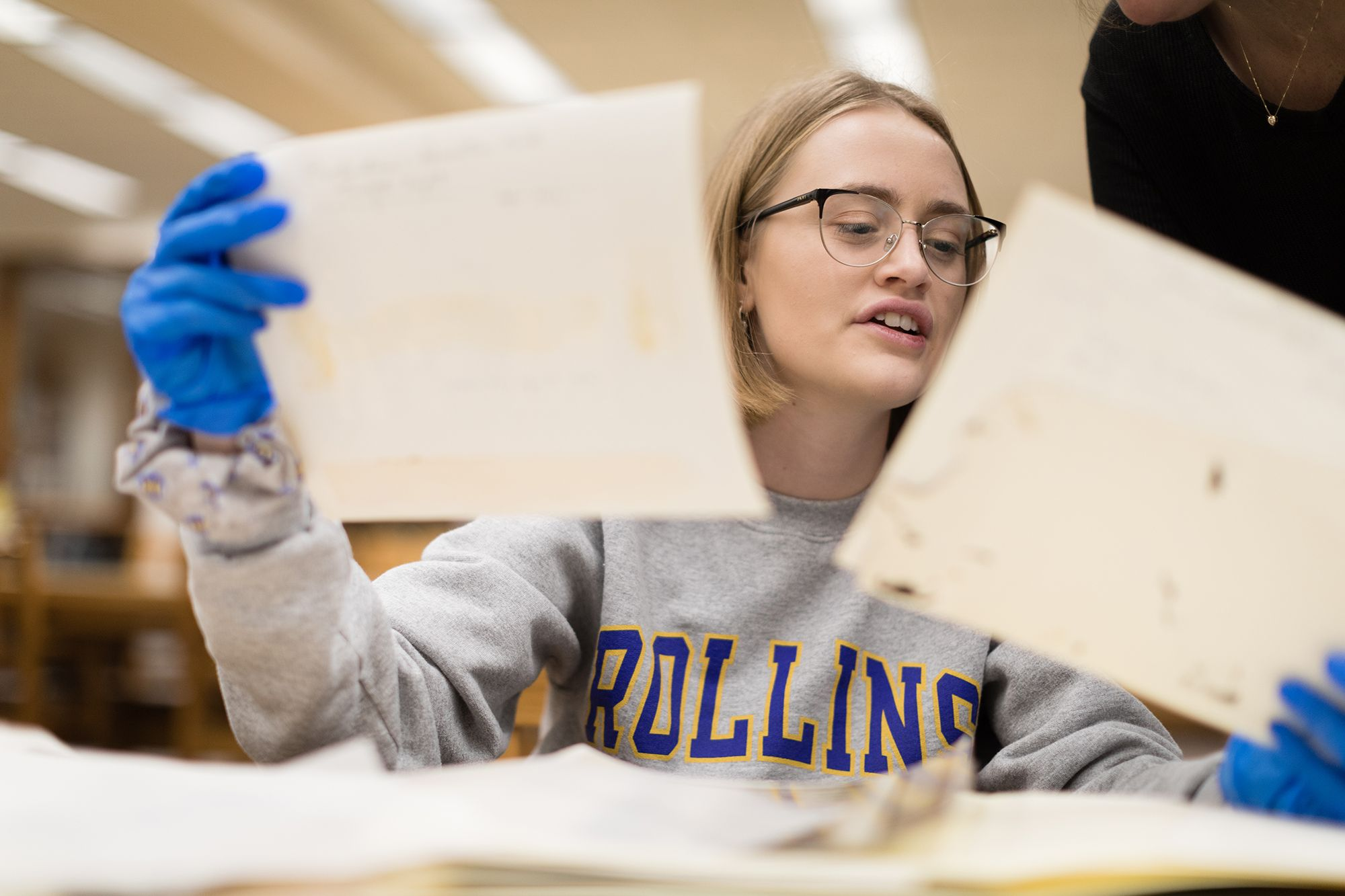 A college student is holding up historical documents in each hand while wearing protective gloves.