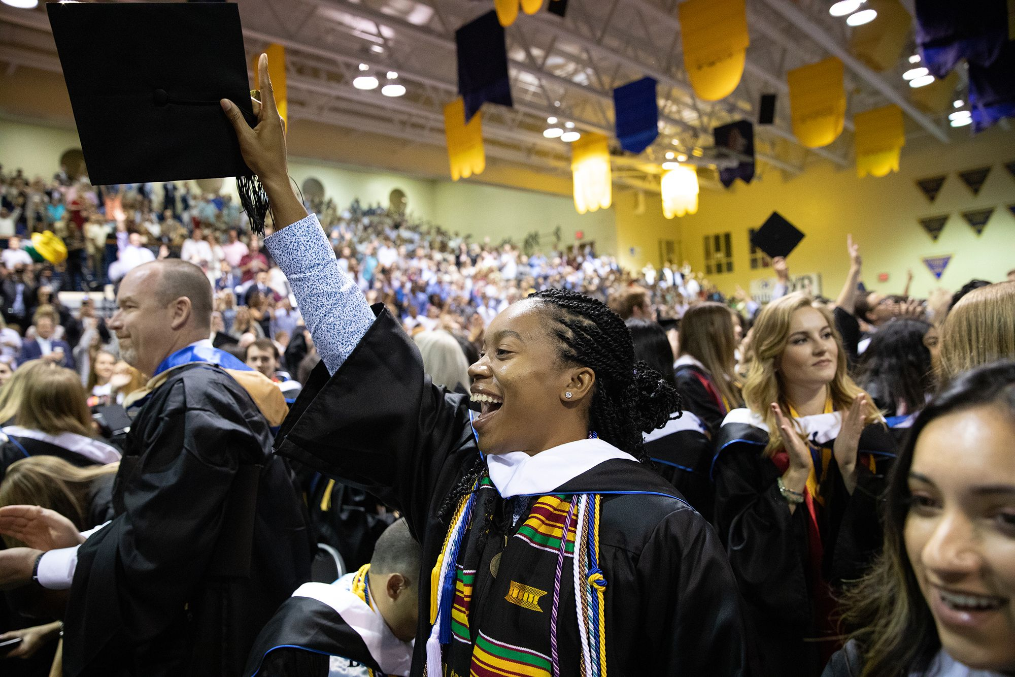 Rollins student holding up diploma on graduation day.