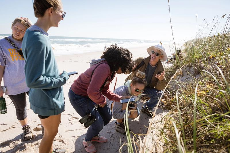 A professor lectures to a group of students during a class at a beach in Florida.