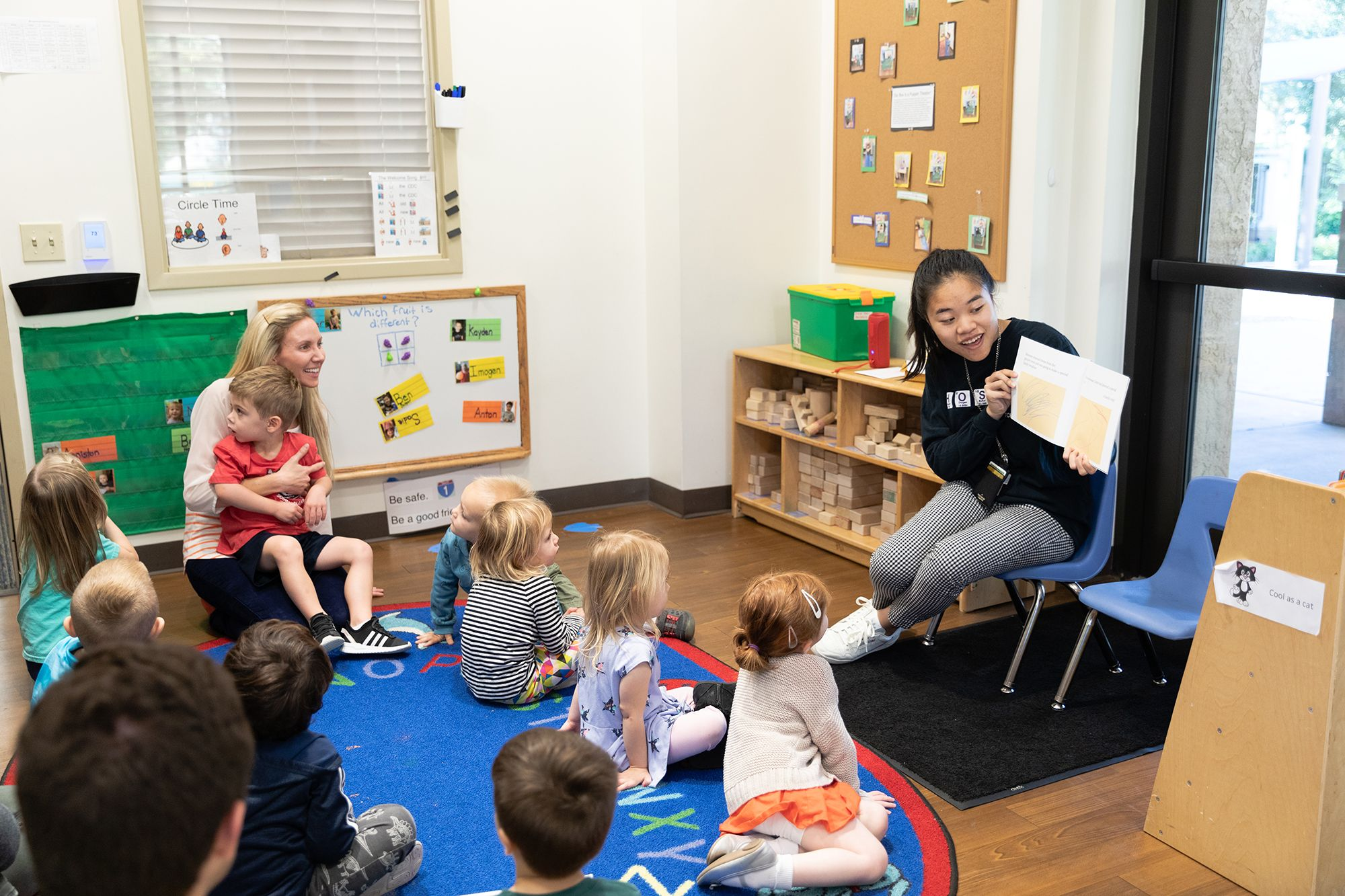 A college student reading to a class of children at the children's development center (CDC).