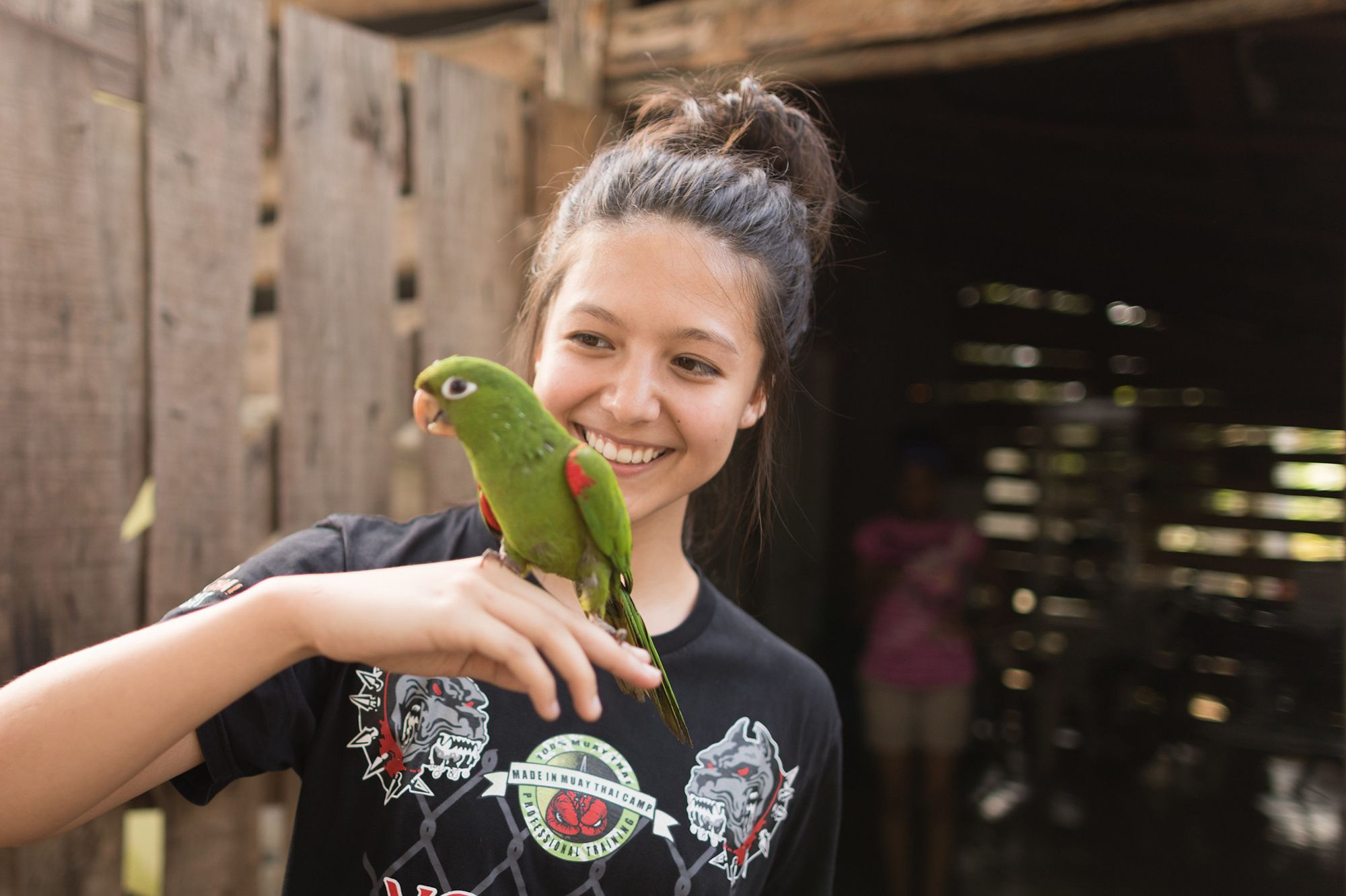A student holding a green parakeet during a Dominican Republic field study.