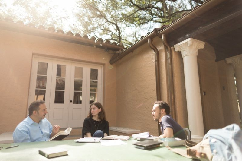 Religious studies college students talking with their professor outside at the table of the outdoor classroom.