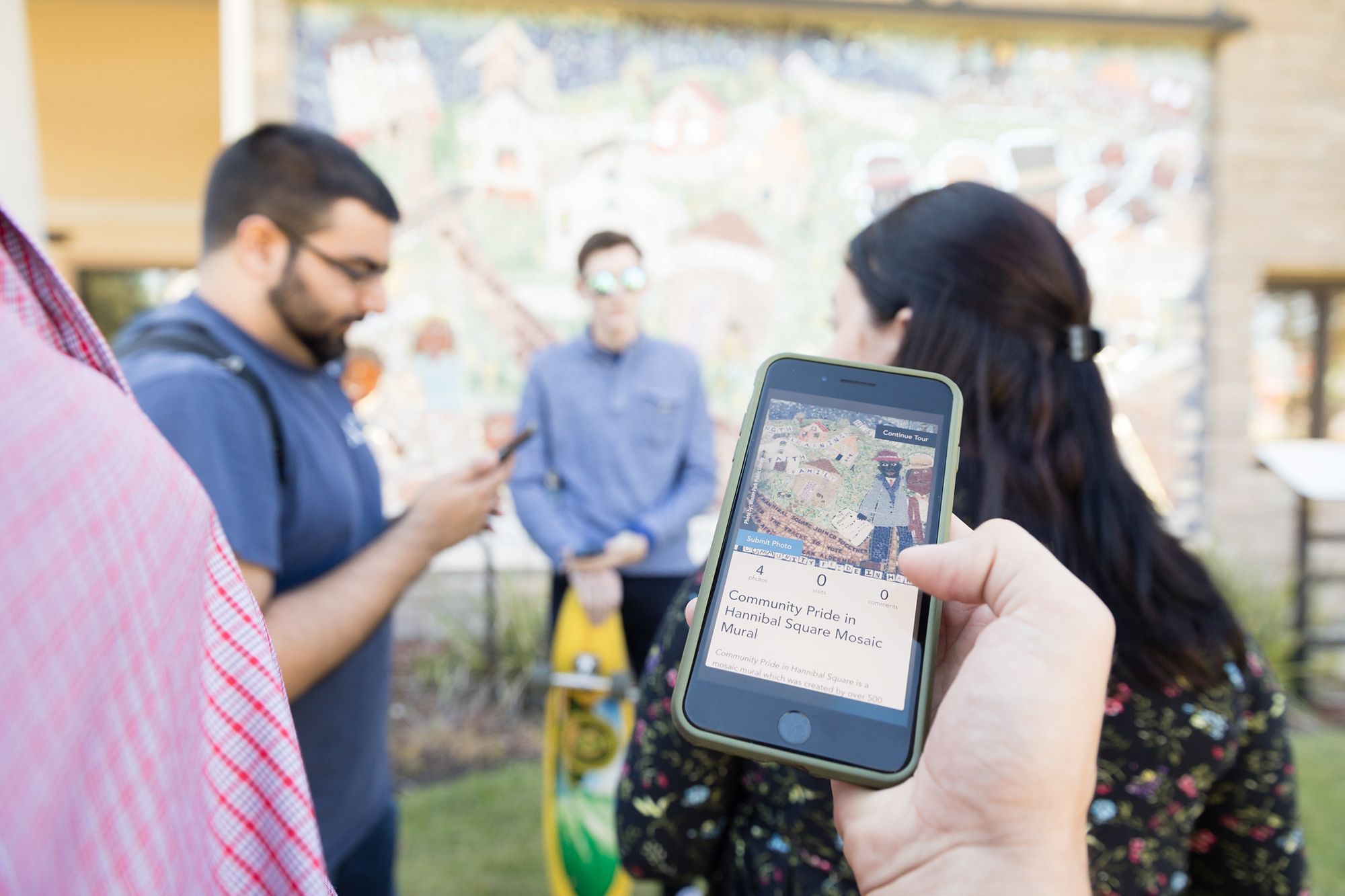 Group of students standing in front of a wall mural. Smartphone with photo of the mural.