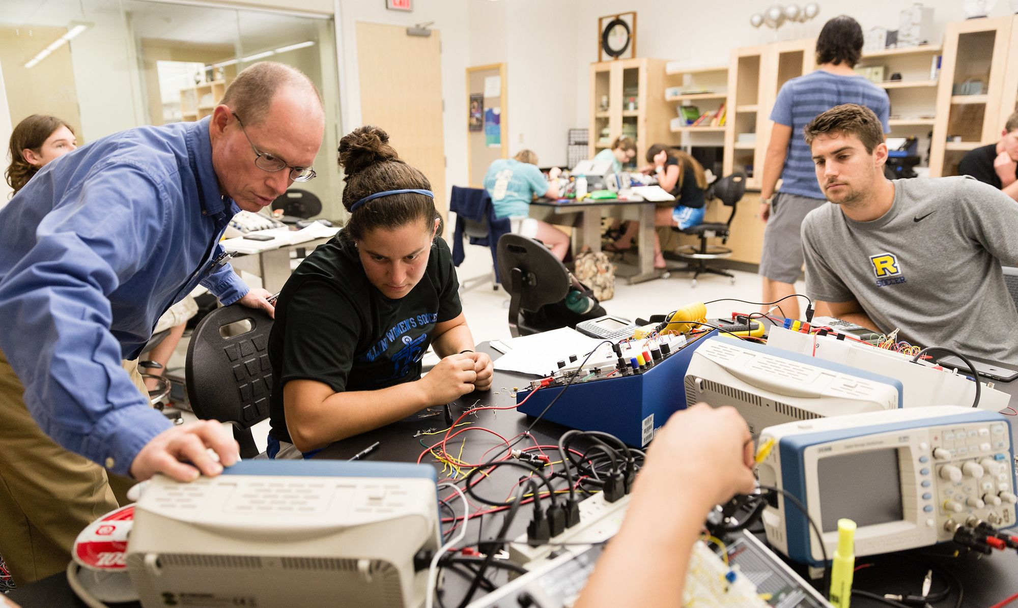A physics professor is looking at a electrical reading with a couple of students in an electronics lab.