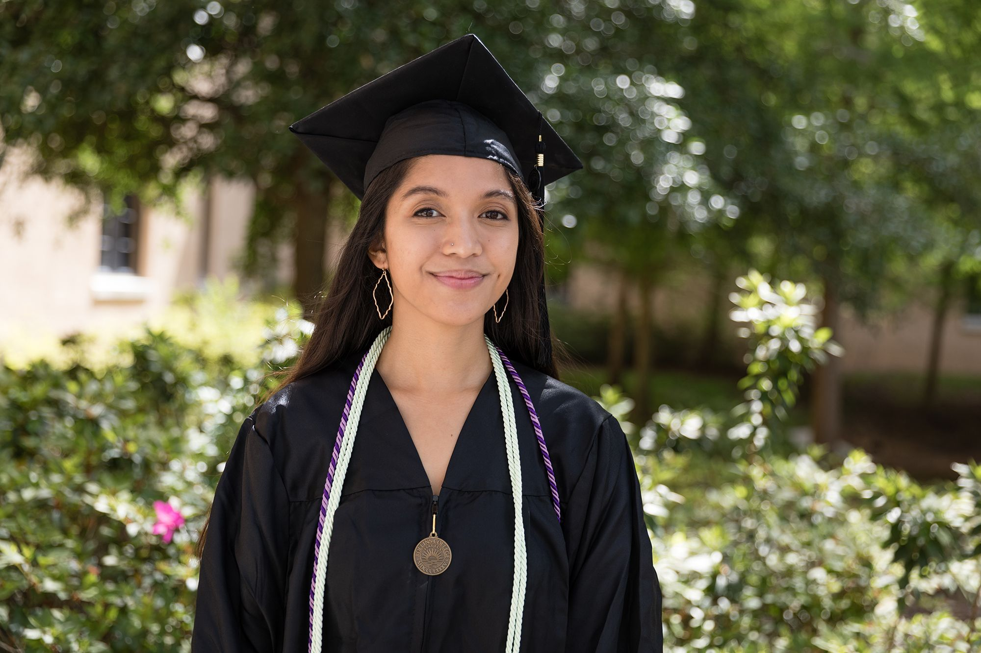 A valedictorian poses on the Rollins College campus.