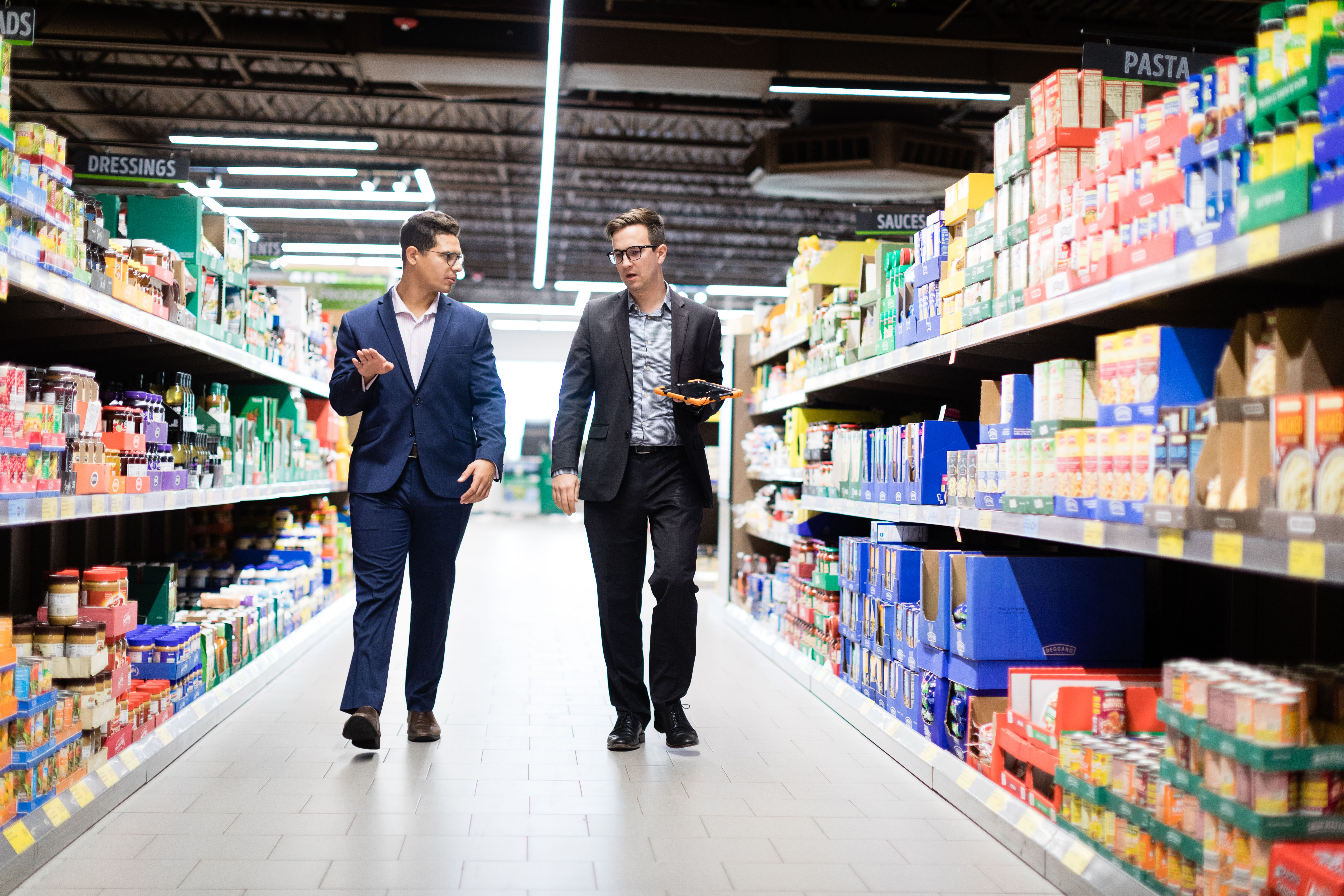 Intern and supervisor walk the aisle at an ALDI store.