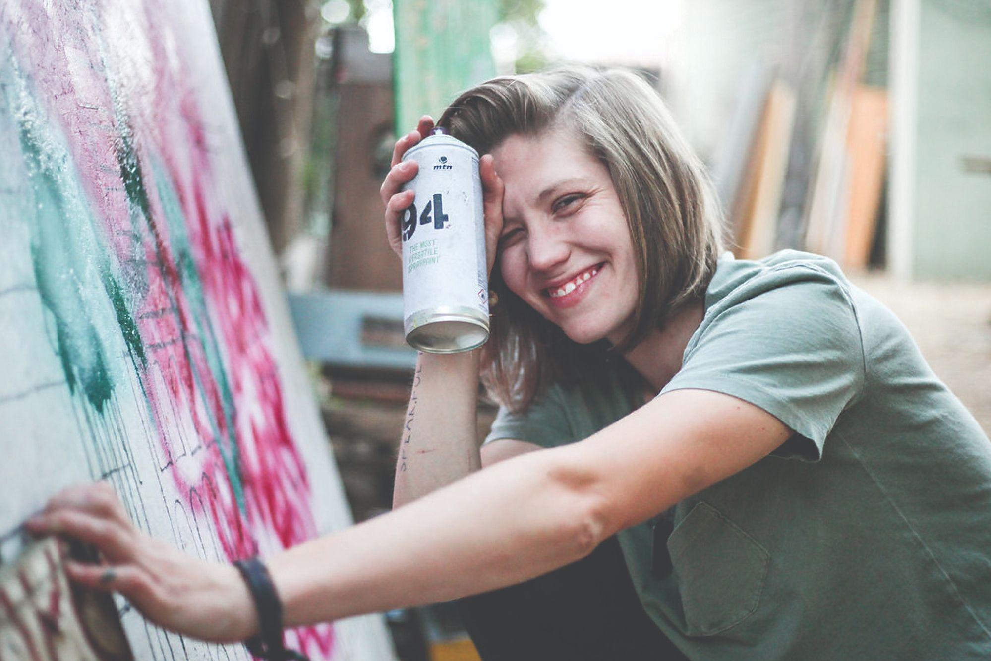 Grace Loescher spray-painting a mural in California.