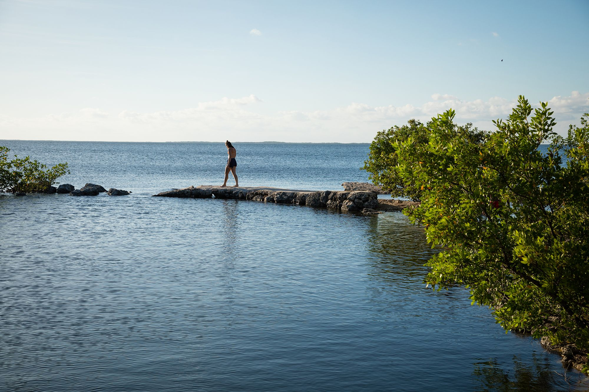 Student walking out on a sandbar over the water in the Everglades.