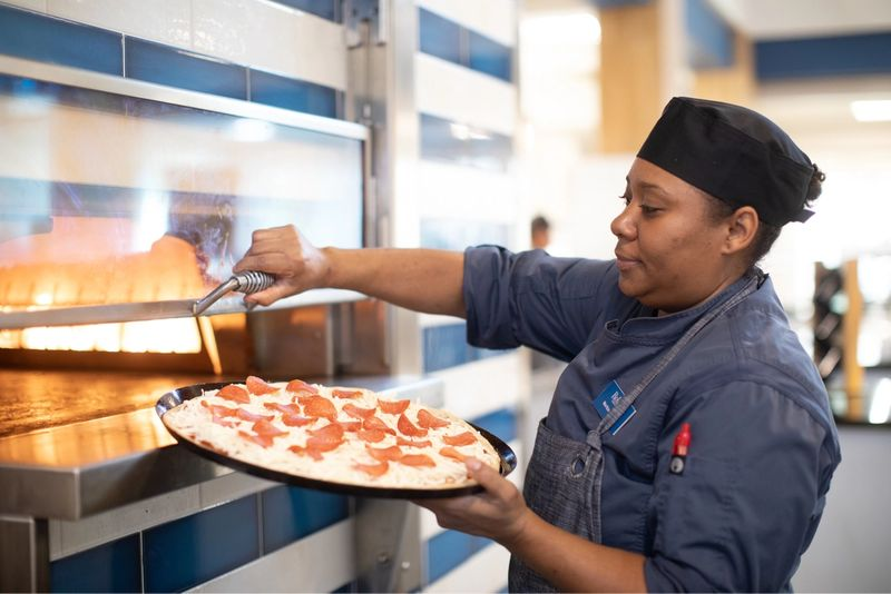 Chef putting a pepperoni pizza into an oven.