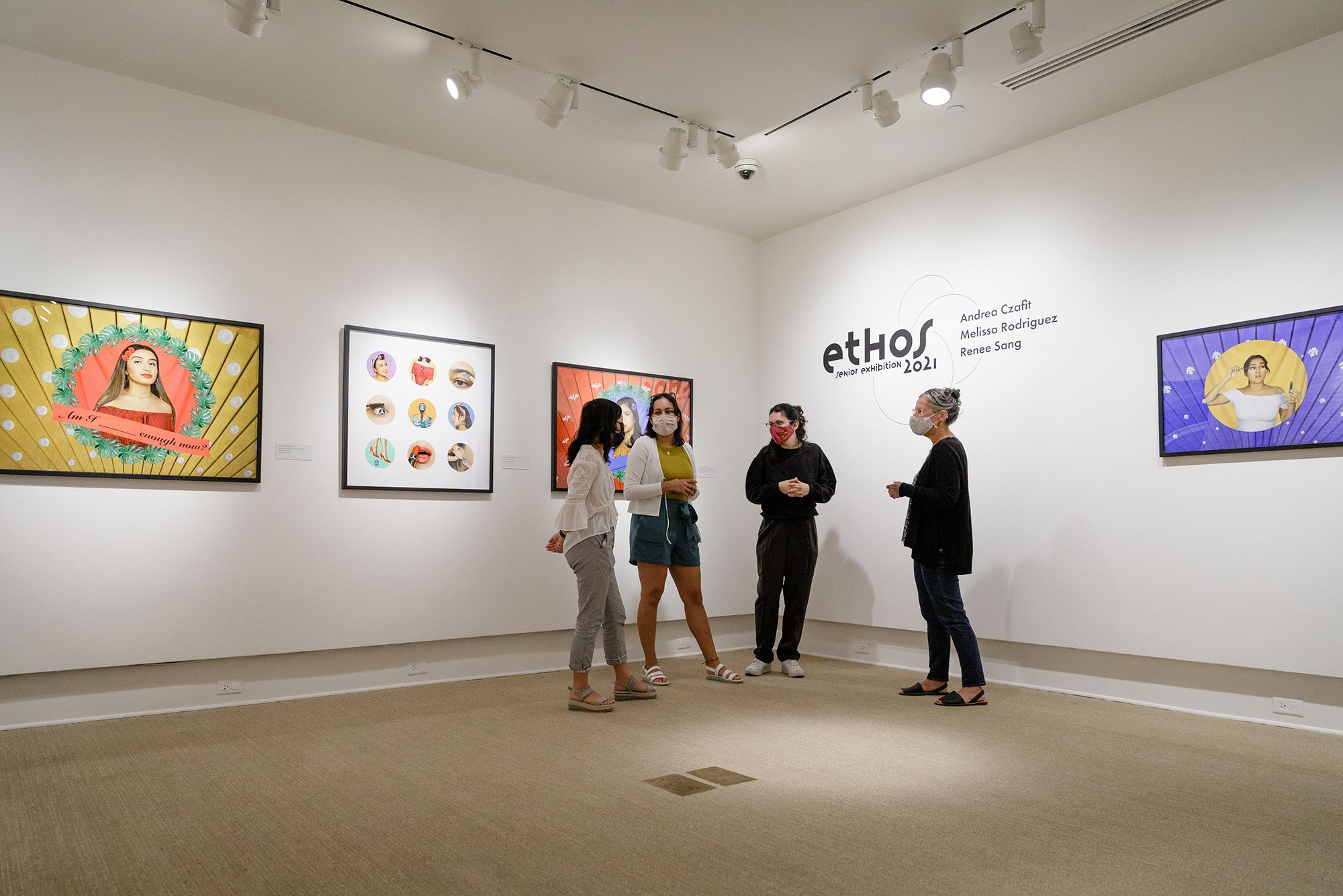 Senior art students pose next to their exhibition in Cornell Fine Arts Museum