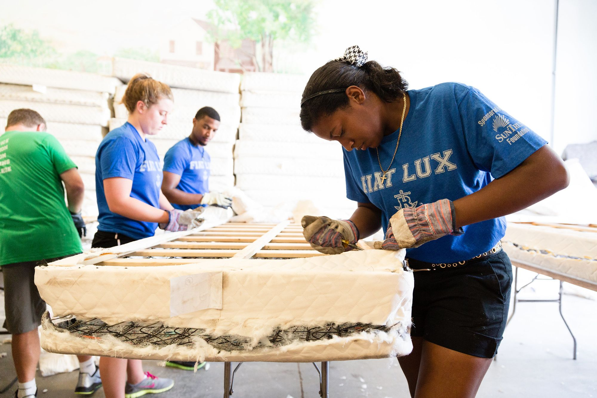 A student recycles a mattress during SPARC Day