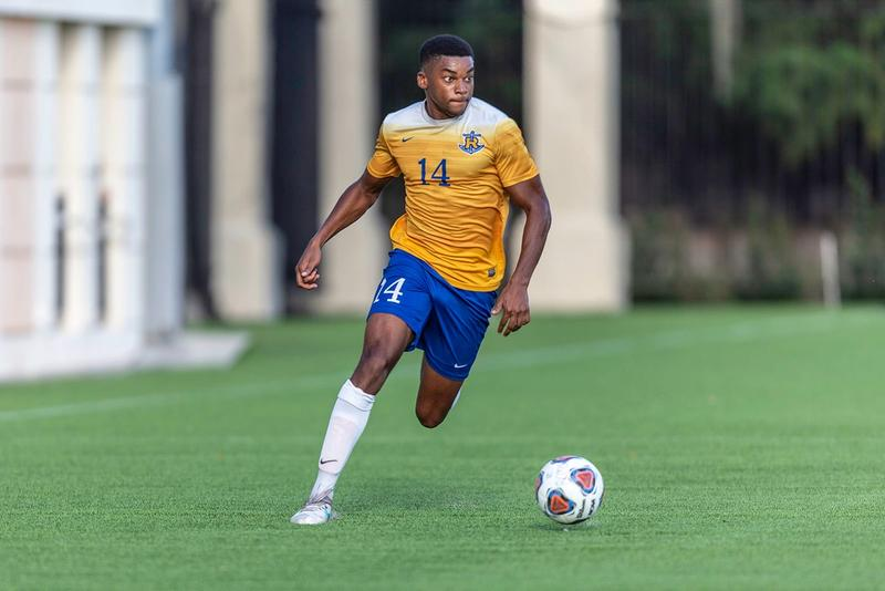 A Rollins soccer player dribbles towards goal.