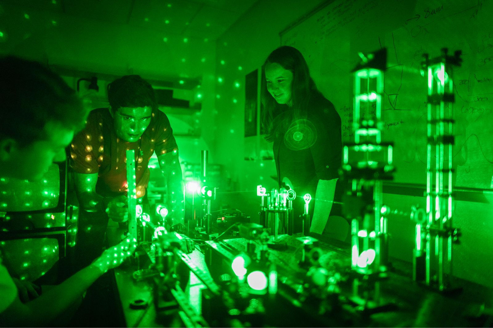A professor and two students conduct physics research.