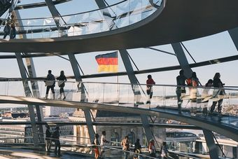 People walk around a modern building in Germany.