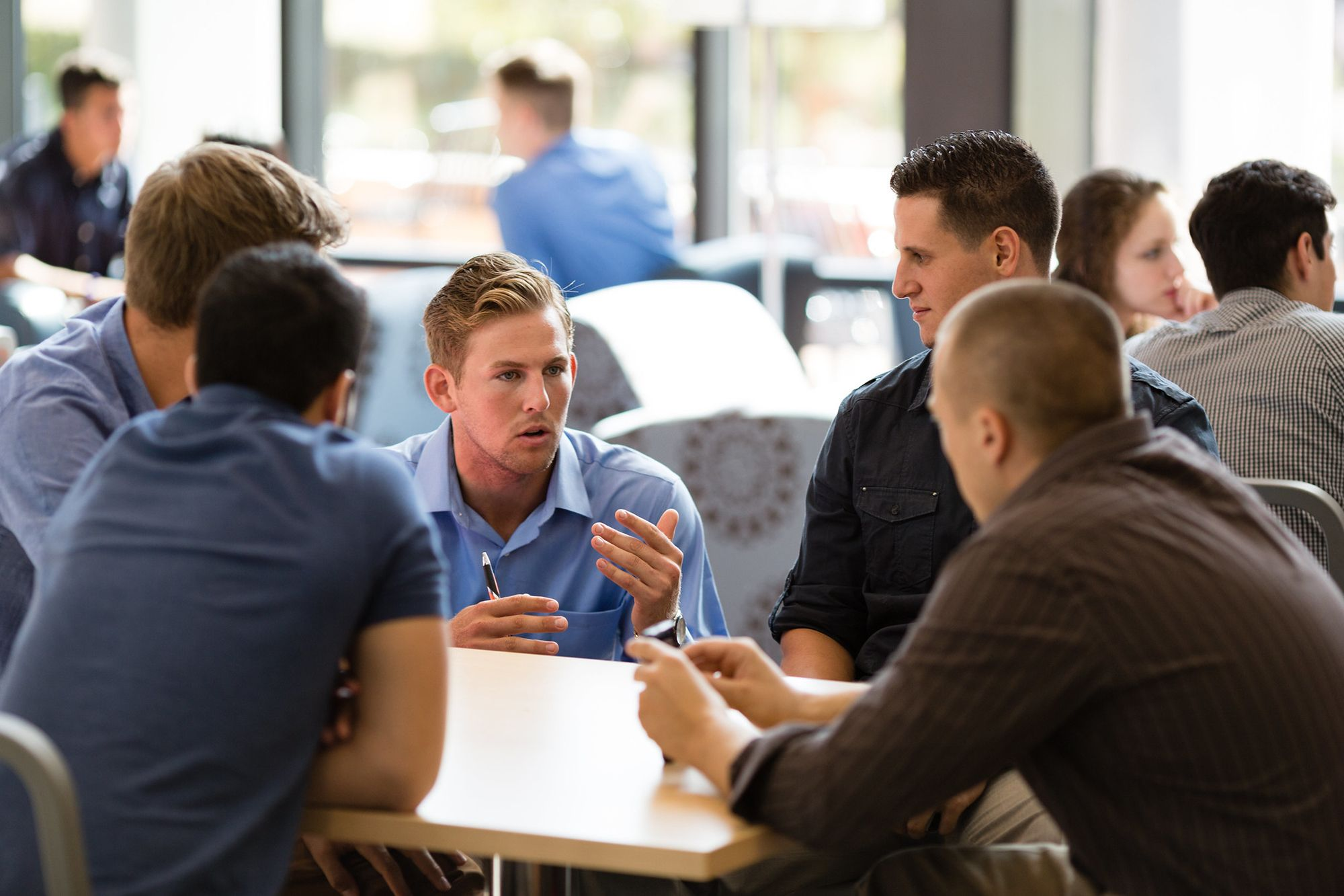A student speaking intently to his colleagues gathered around a table.