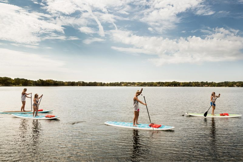 A group of four students paddle boards on Lake Virginia.
