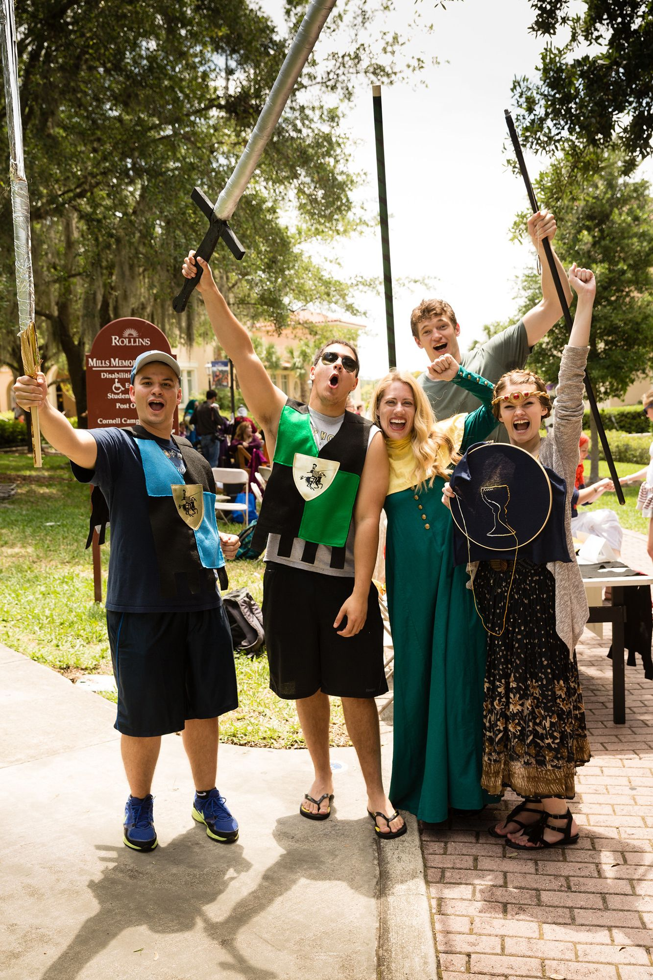 Professor, Jana Matthew, and students dressed in medieval attire holding up their swords and shields.