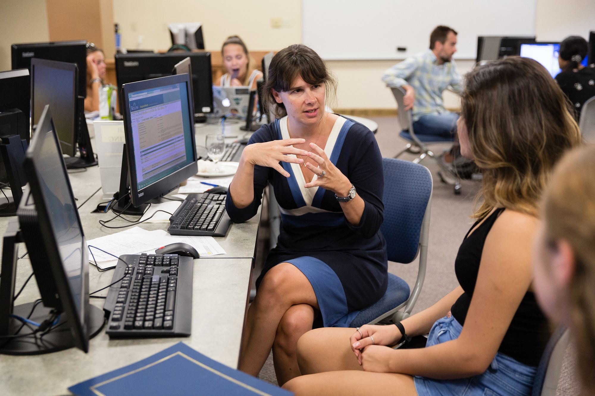 A college professor is sitting with her students in a computer lab explaining a problem.