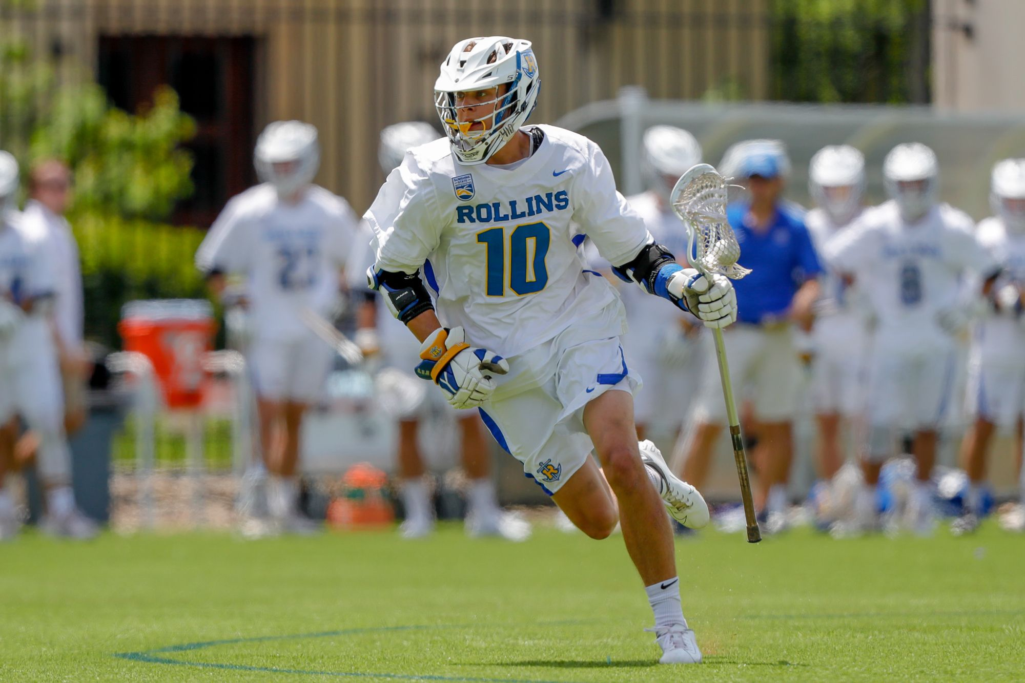 Greg Taicher fully dressed in his Rollins Lacrosse uniform running on the field.