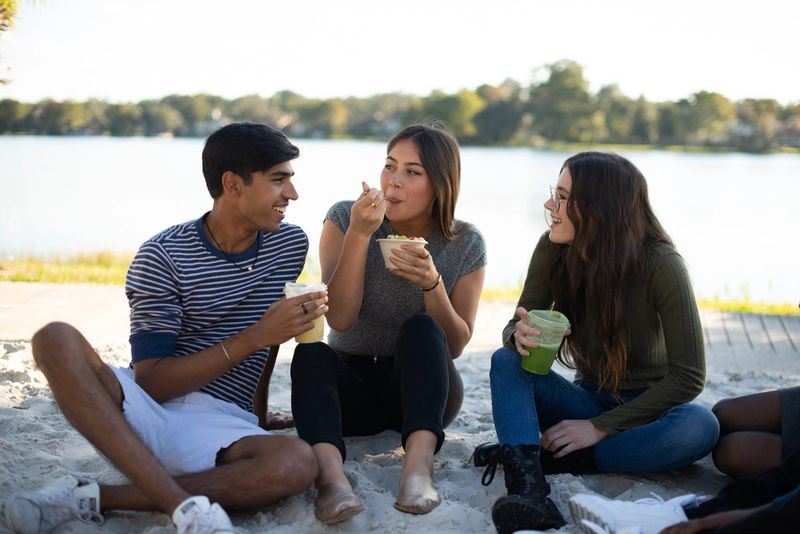 Three students sitting and enjoying a meal by Lake Virginia.