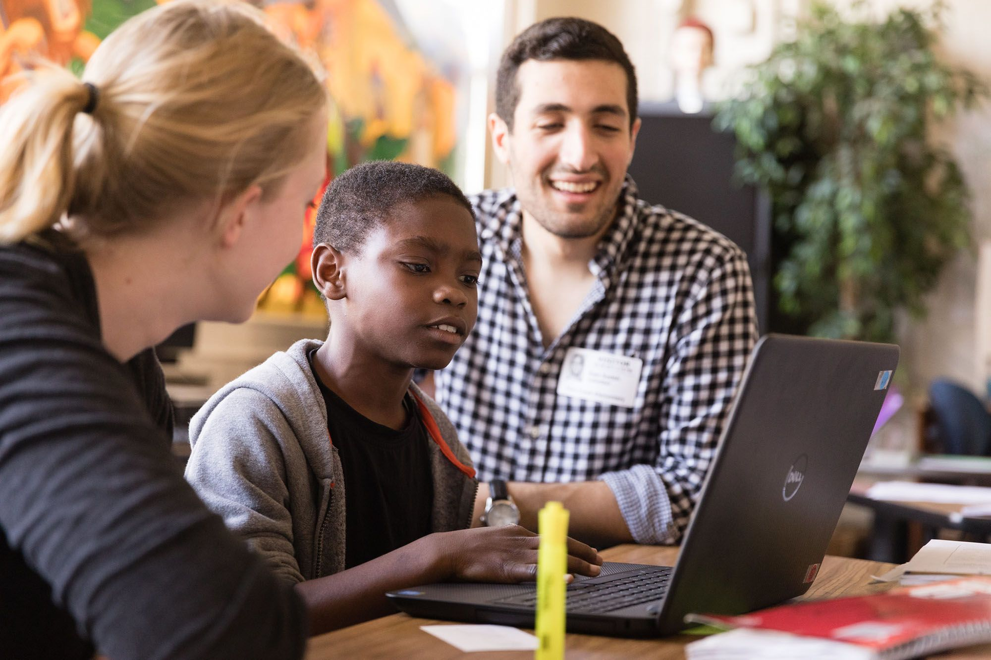 Sam Sadeh '18 teaches a child how to code as part of funding made possible by Google.