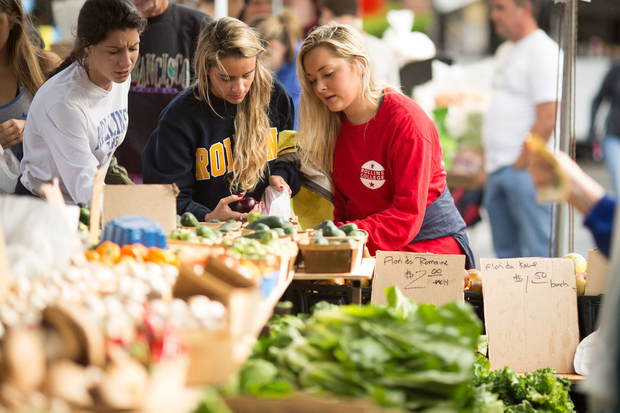 Three students shop for produce at the Winter Park Farmer's market.