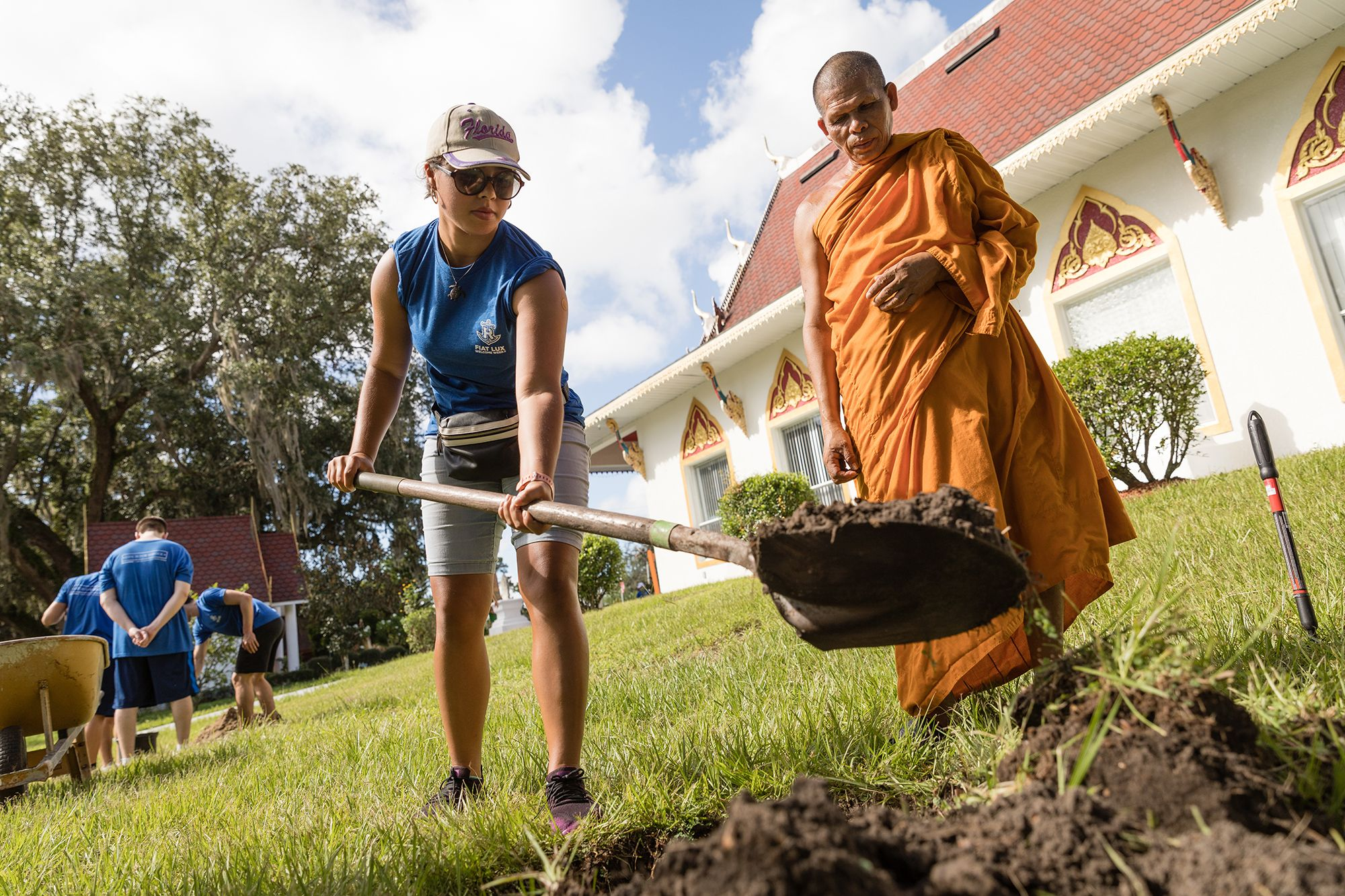 College students helping plant trees at a local Orlando Buddhist Temple.