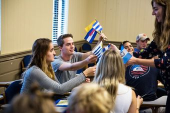Hispanic Studies professor passing out Latin American flags in class to students.