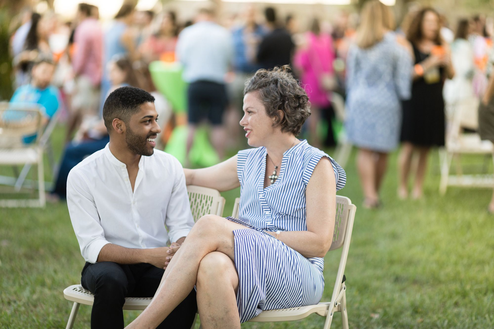 Two students sitting and talking to each other at an outdoor event on the lawn.