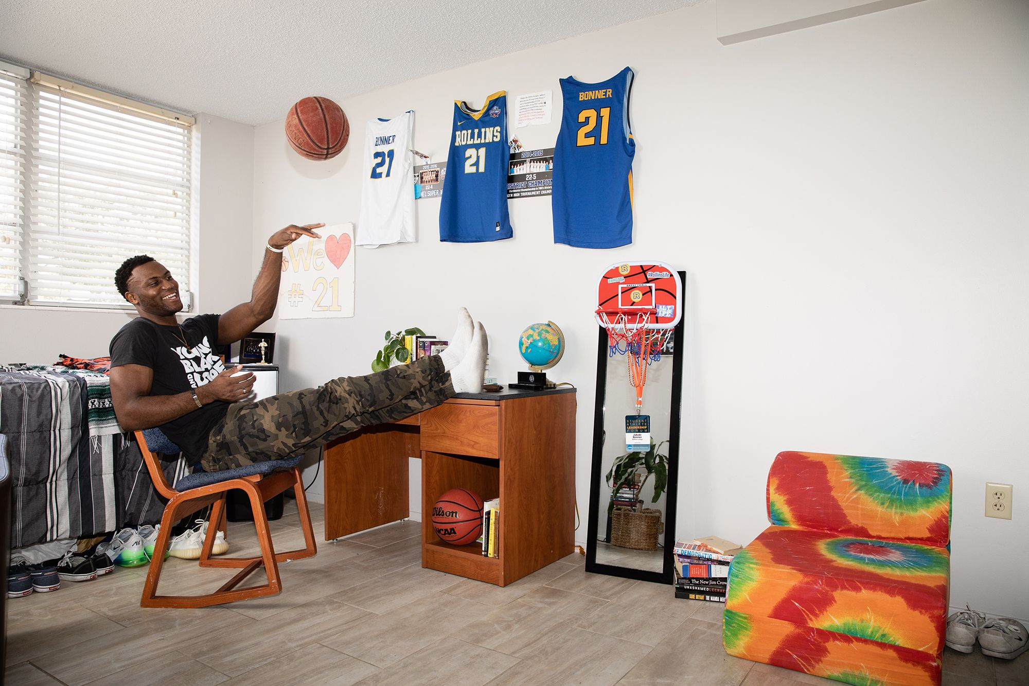 A player on the basketball team shooting a basketball in his dorm room.