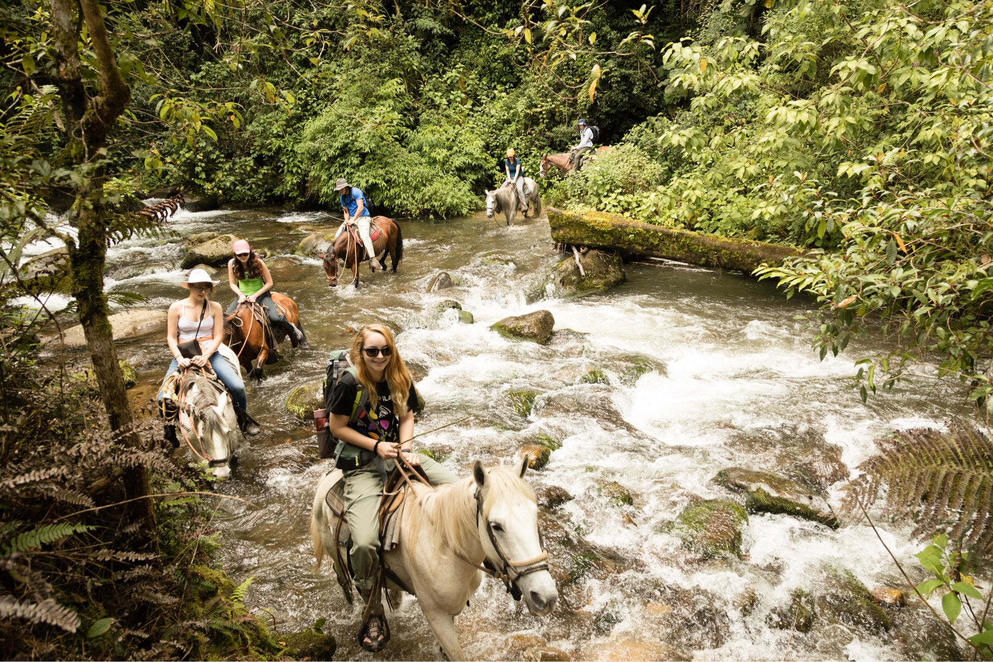 Students cross a river on horseback in a Costa Rican rainforest.