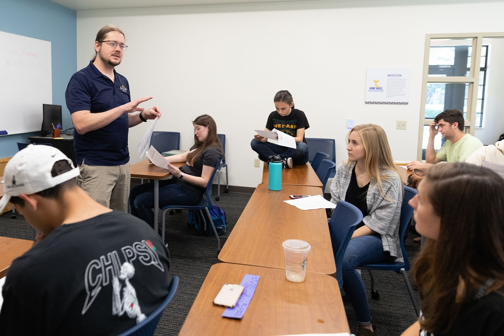 Professor Matthew Forsythe speaking to his class of students sitting at their desks.