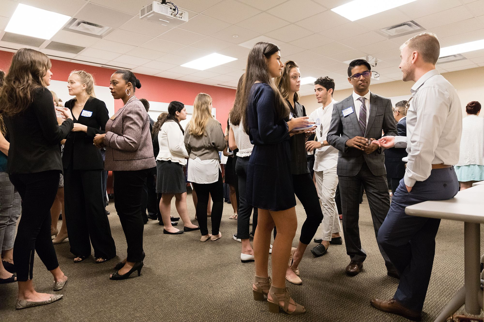 A group of students dressed in business attire talking and networking.