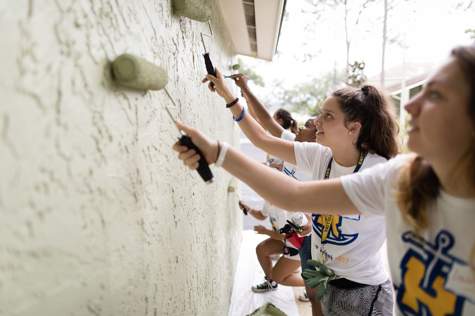 Liberal Arts college students serving others by painting a local school.
