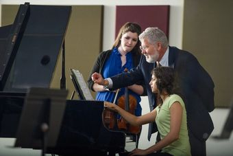 Music professor John Sinclair instructs students at a piano.