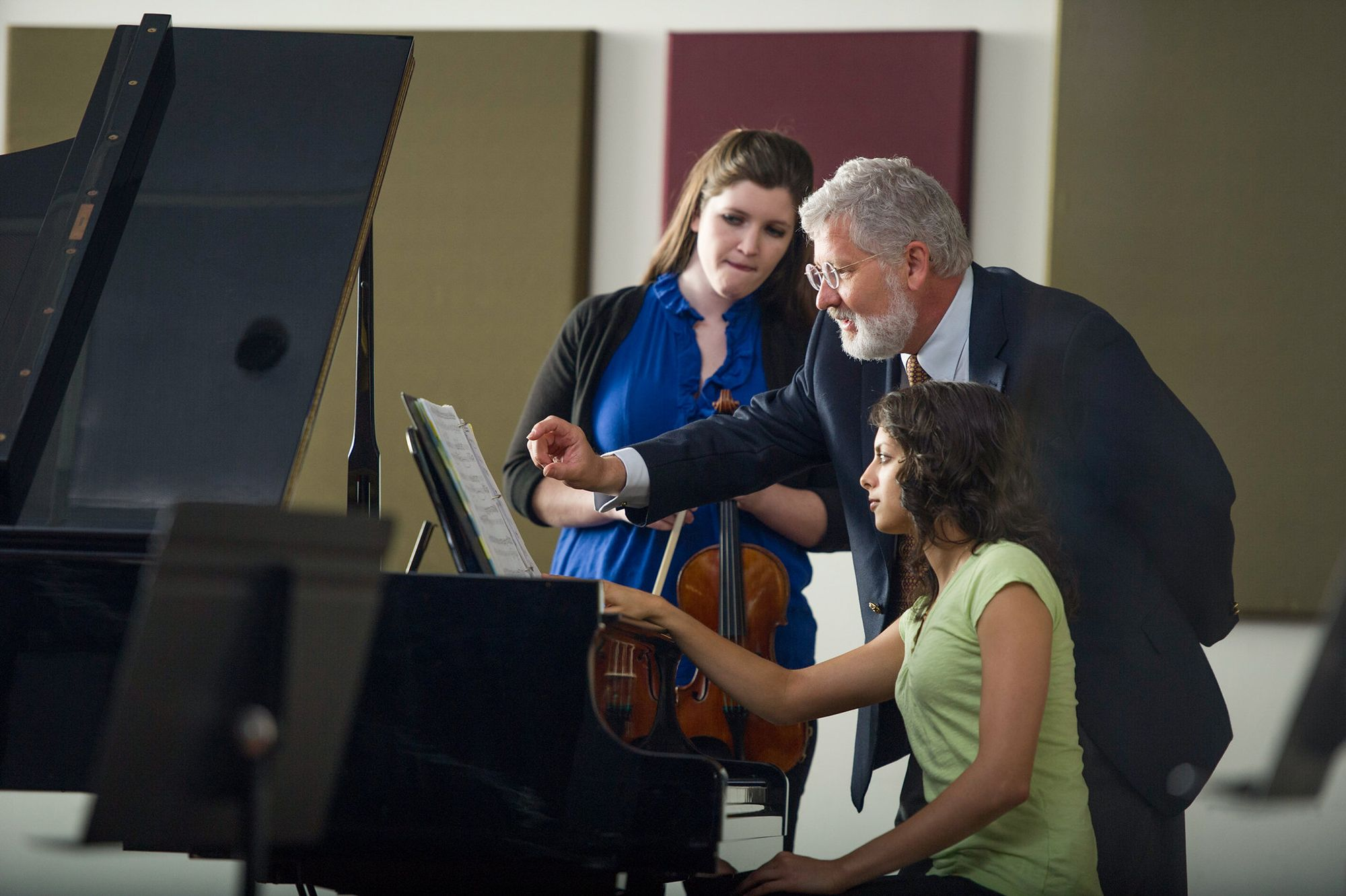 Music director and mentor, John Sinclair, reading sheet music at a piano with two college students.