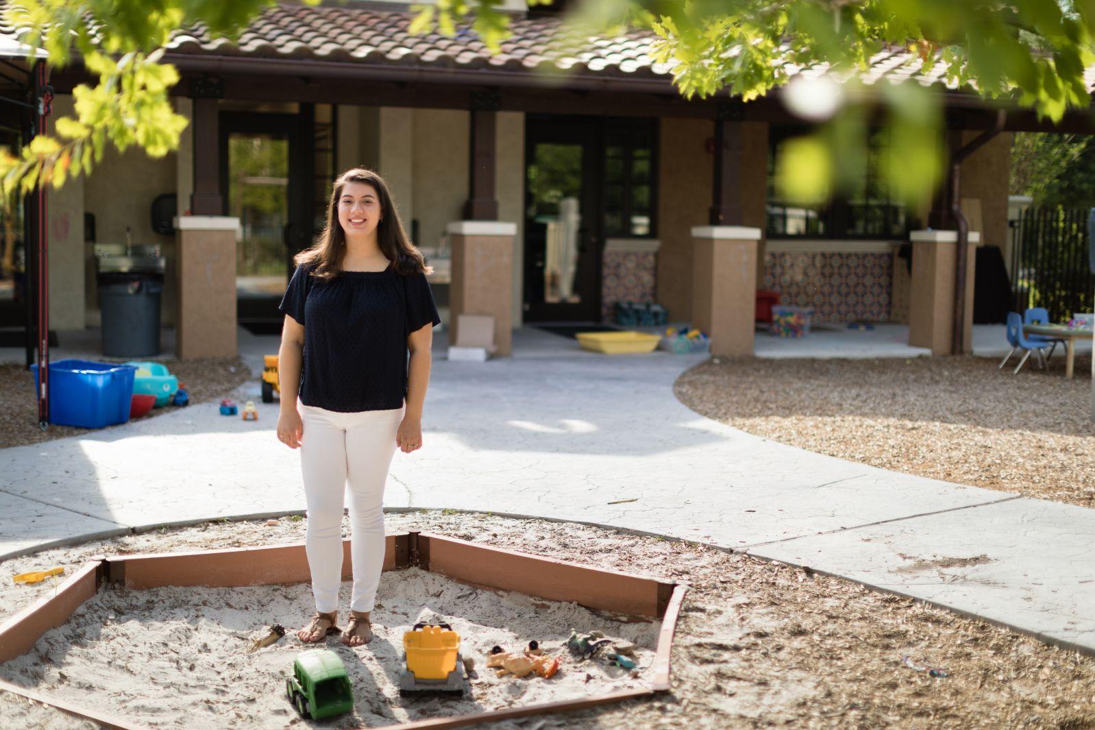Alexandria Tomkunas '18 sits on the edge of a sandbox