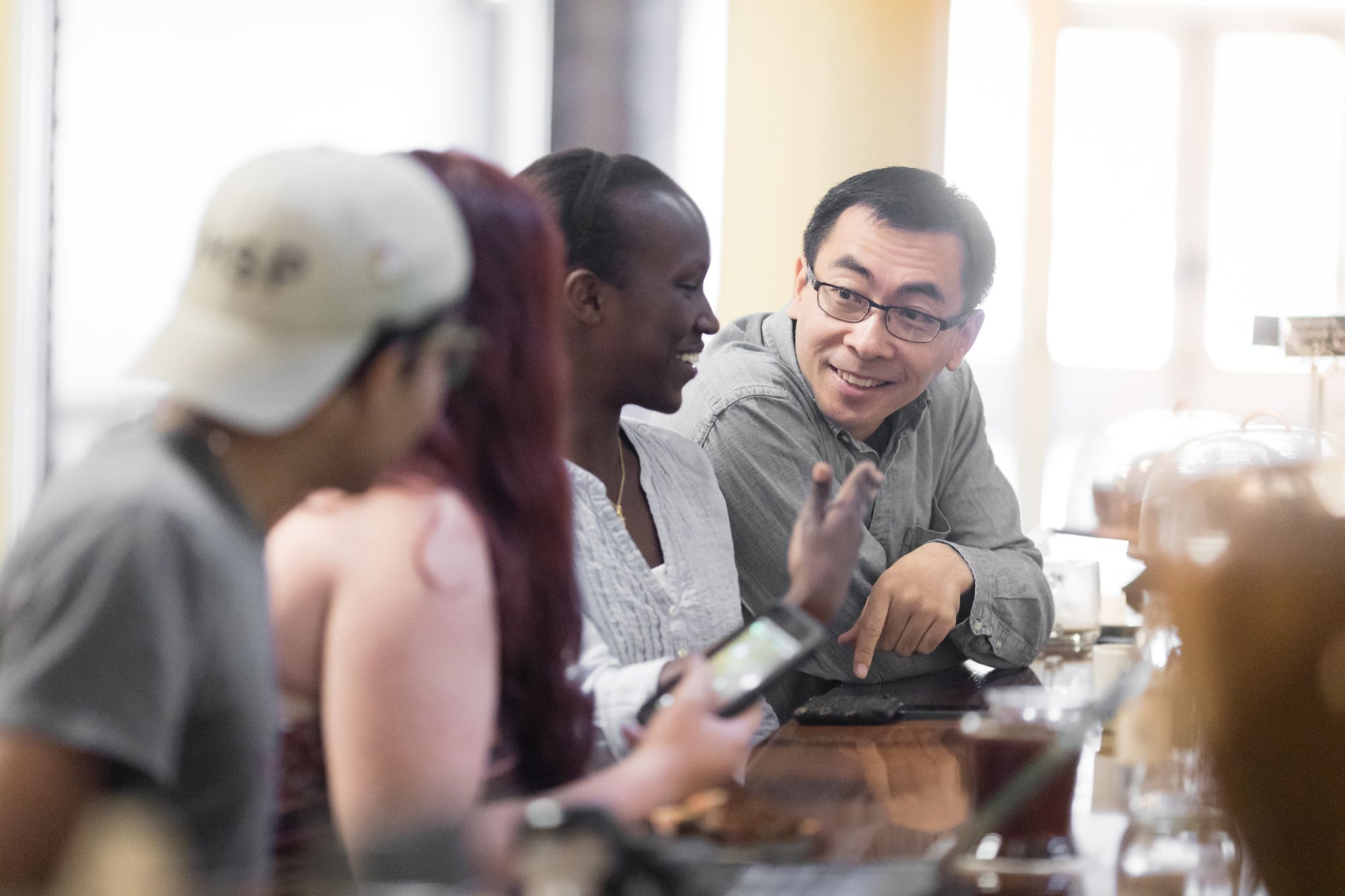 An economy college professor is talking with his students at a local cafe.
