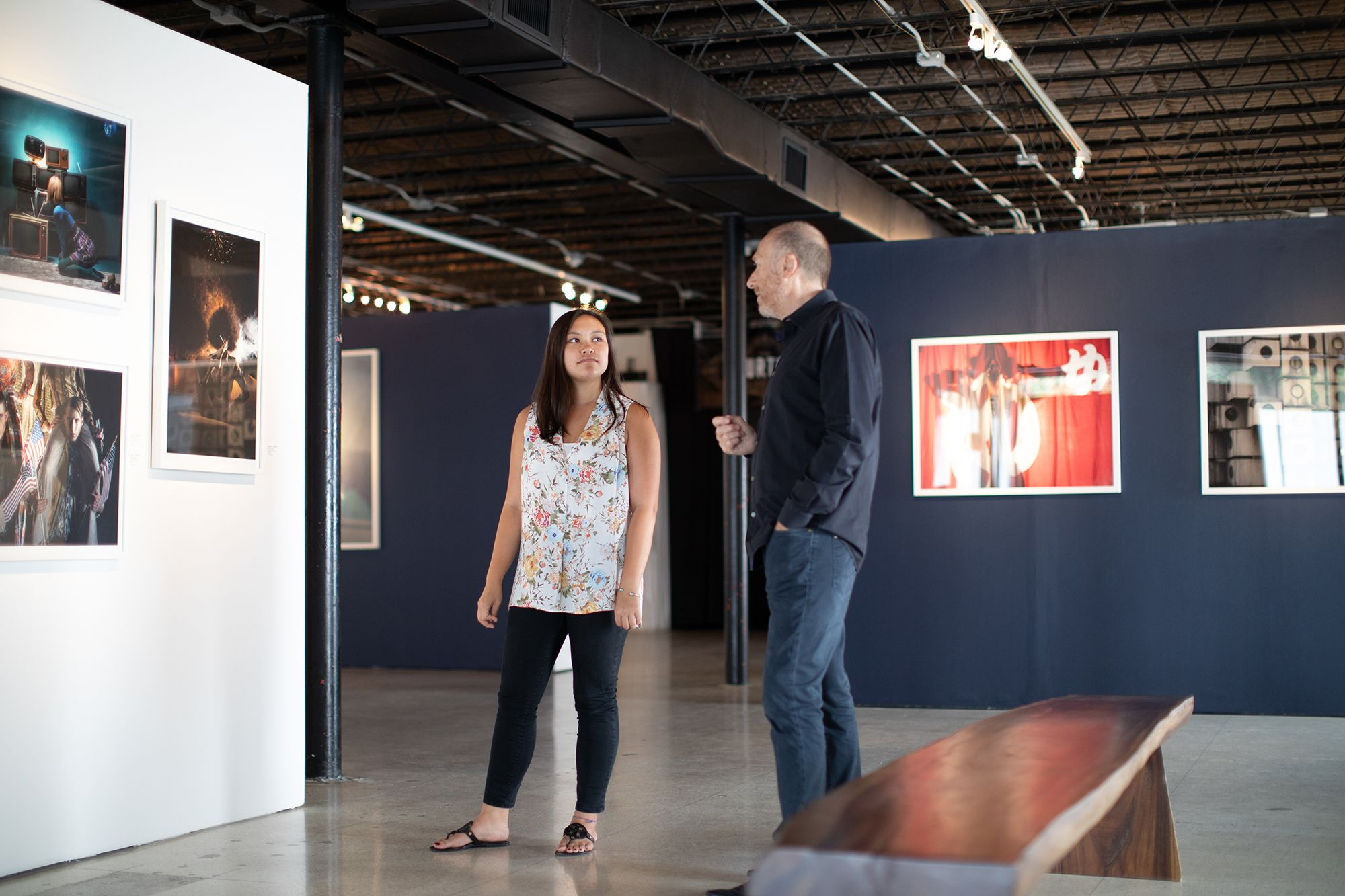 A student intern and an art gallery owner discuss an artwork.