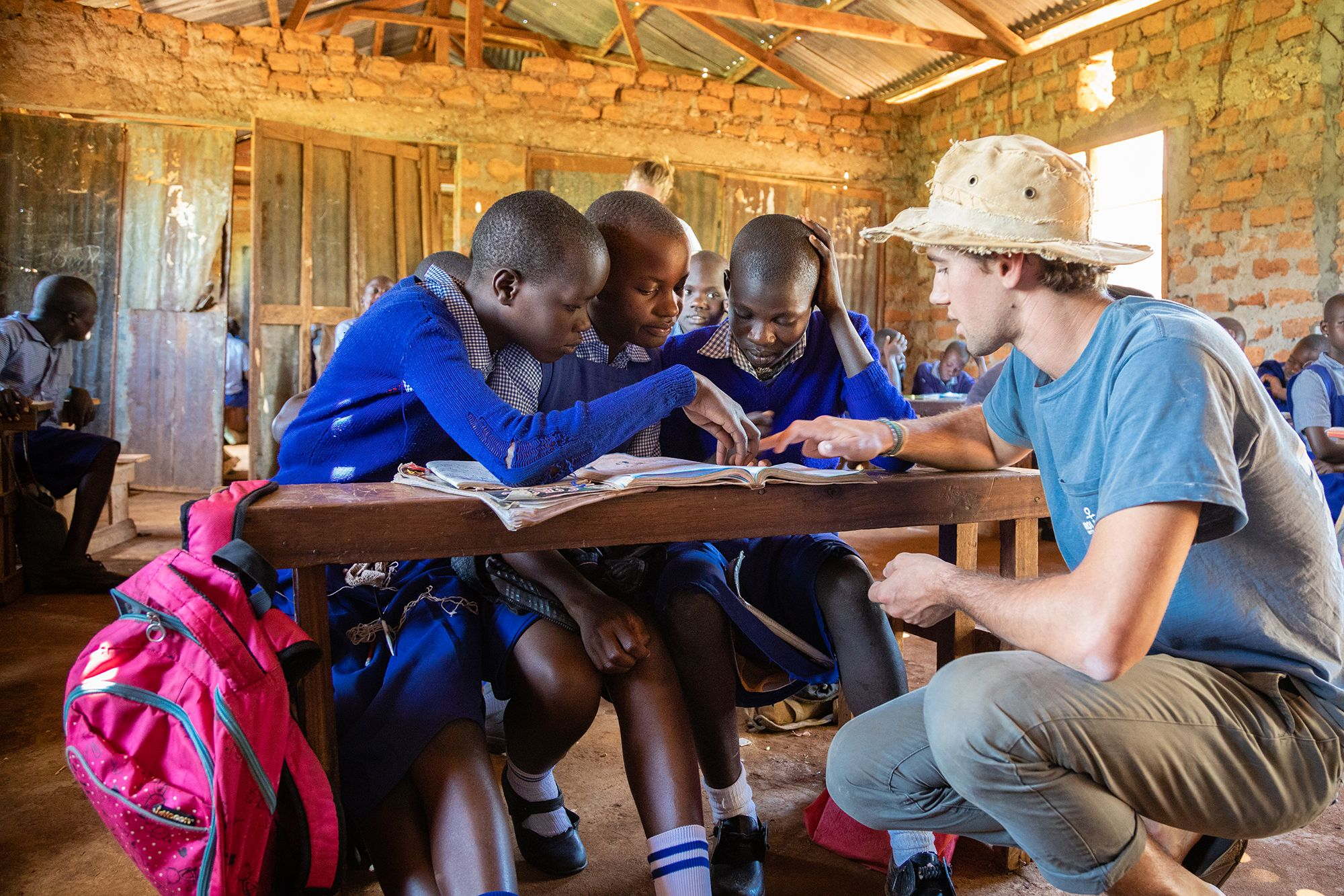 A student teaching several local children on a field study in Tanzania.