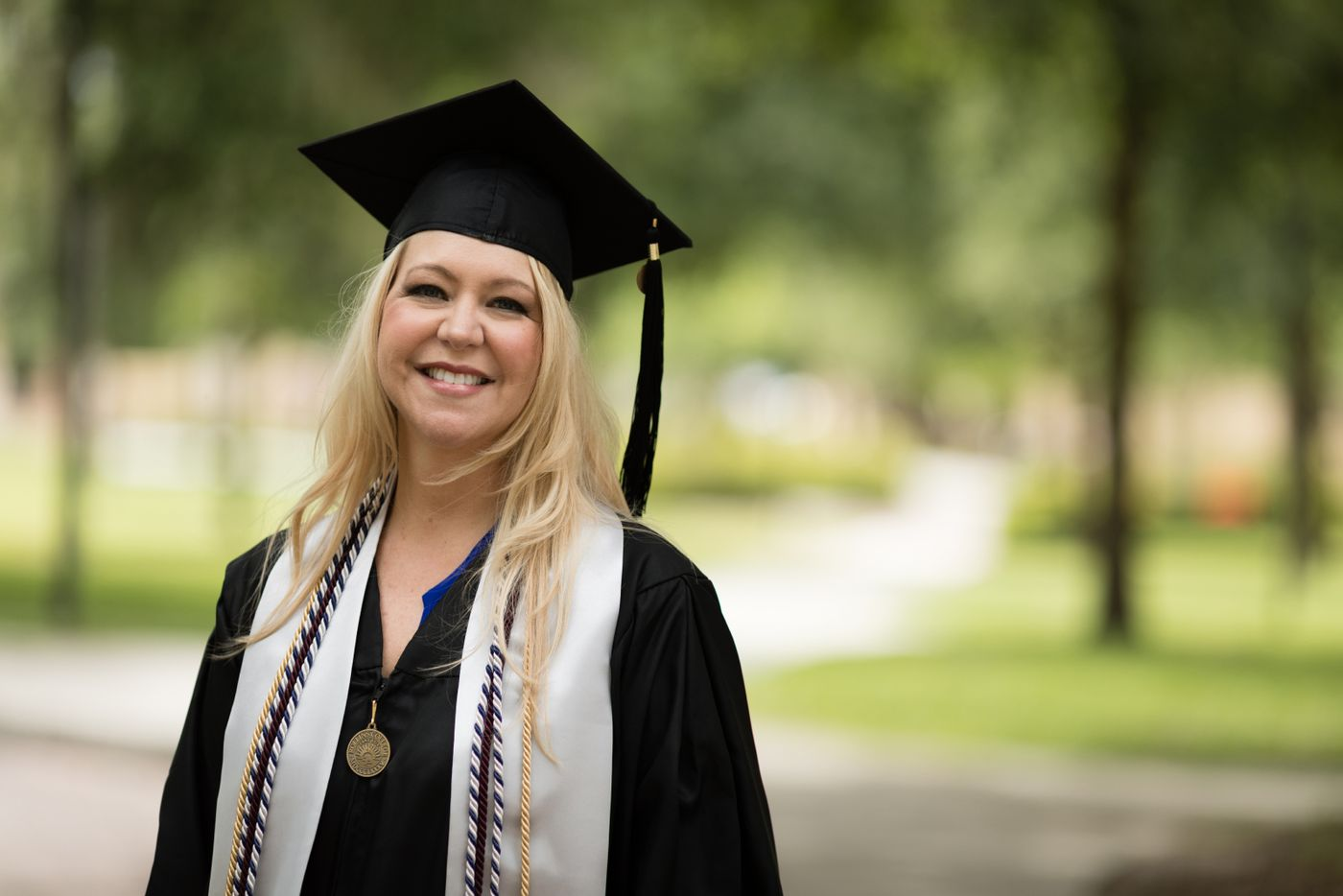 Shannon Burrows outside on campus wearing a cap and gown for commencement.