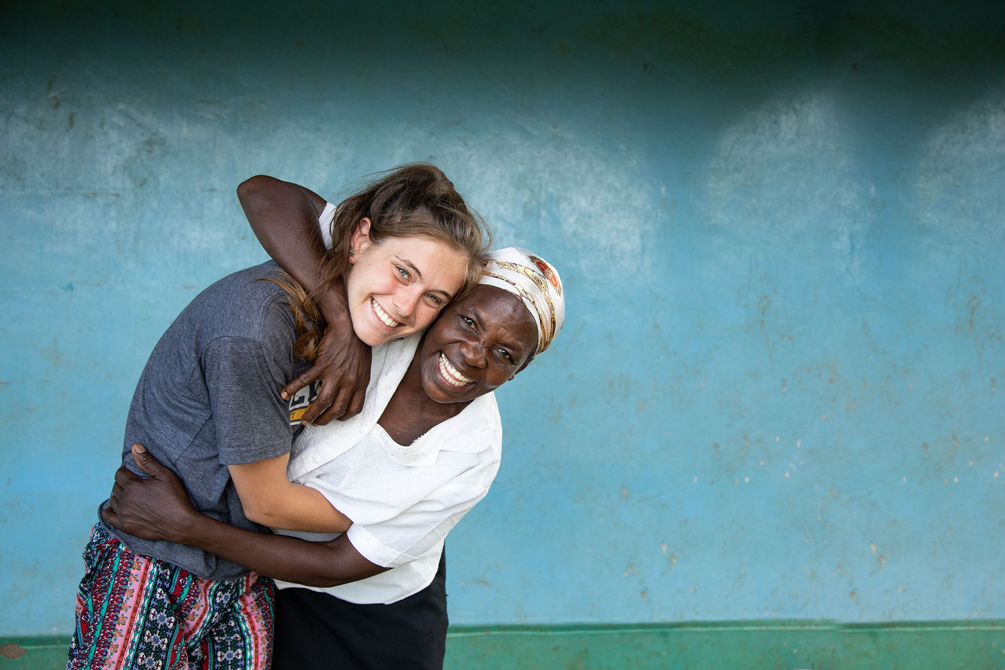 A student and a local Tanzanian embrace after forming a newfound connection.