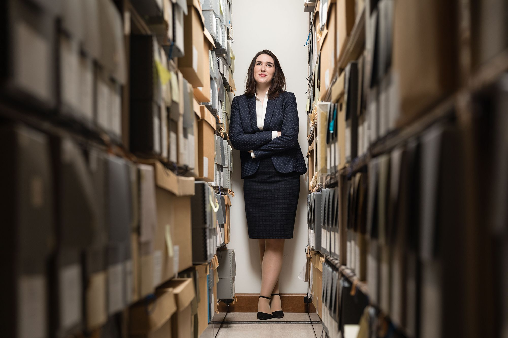 Rebecca Charbonneau '16 portrait among boxes of art history archives and materials.