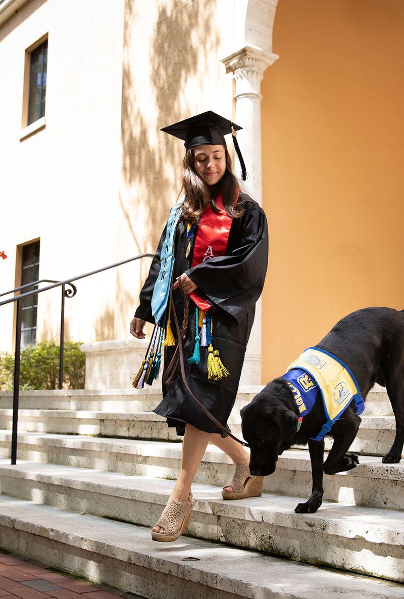 Marissa Cobuzio '19 walks her service dog, Ari, down stairs on the Rollins campus.