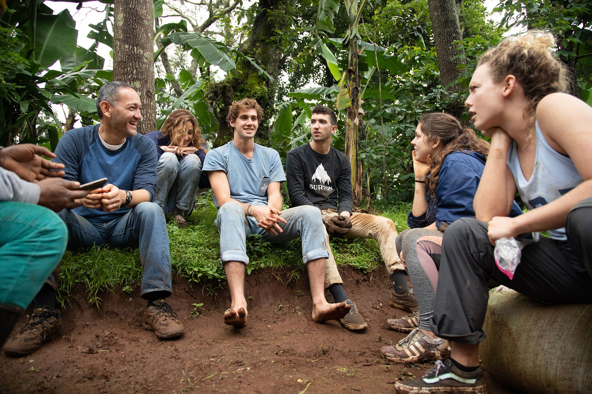 A professor and his students sit in a circle and talk during a field study in Tanzania.
