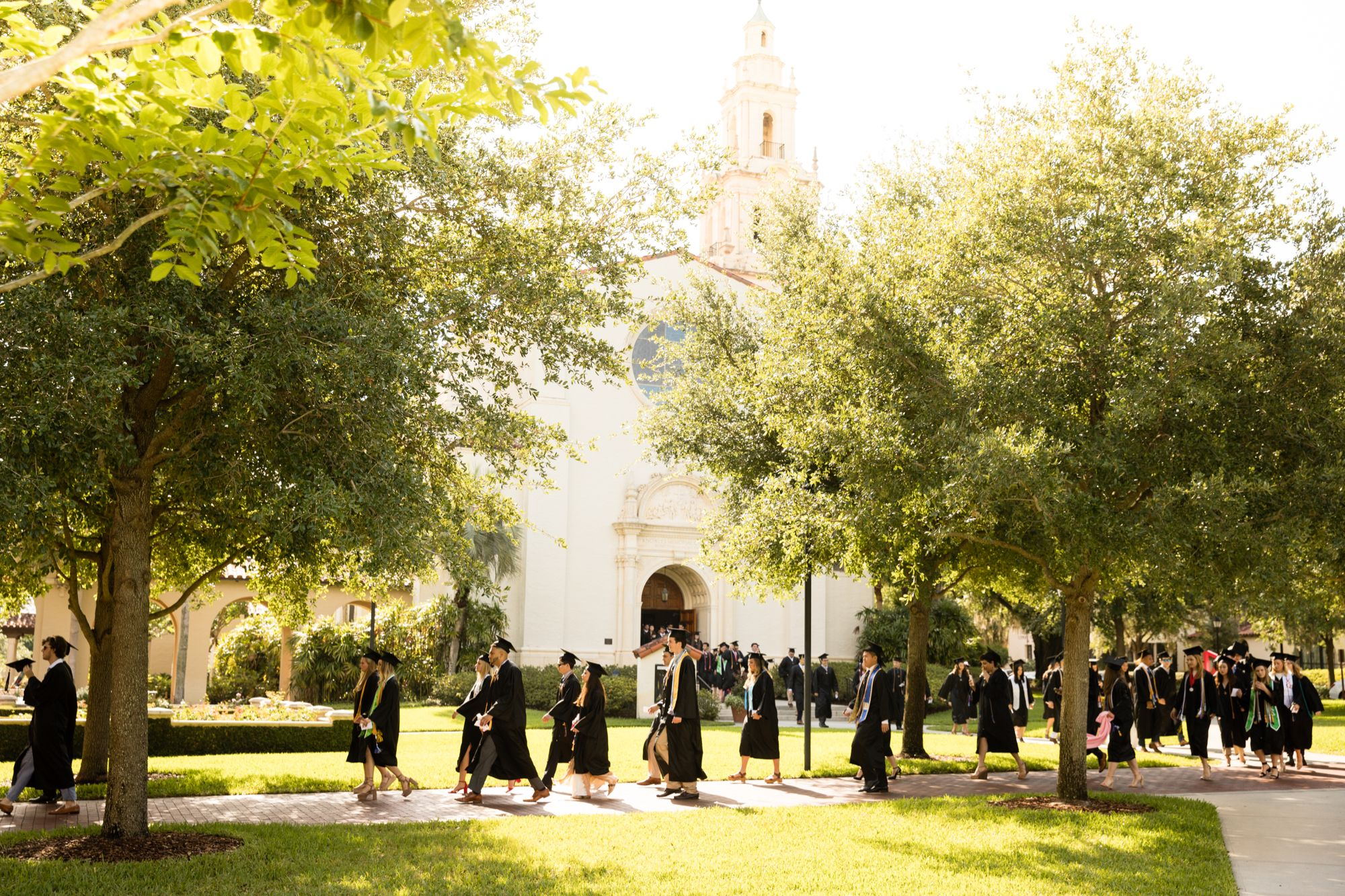 Rollins students walk past the rose garden during commencement.
