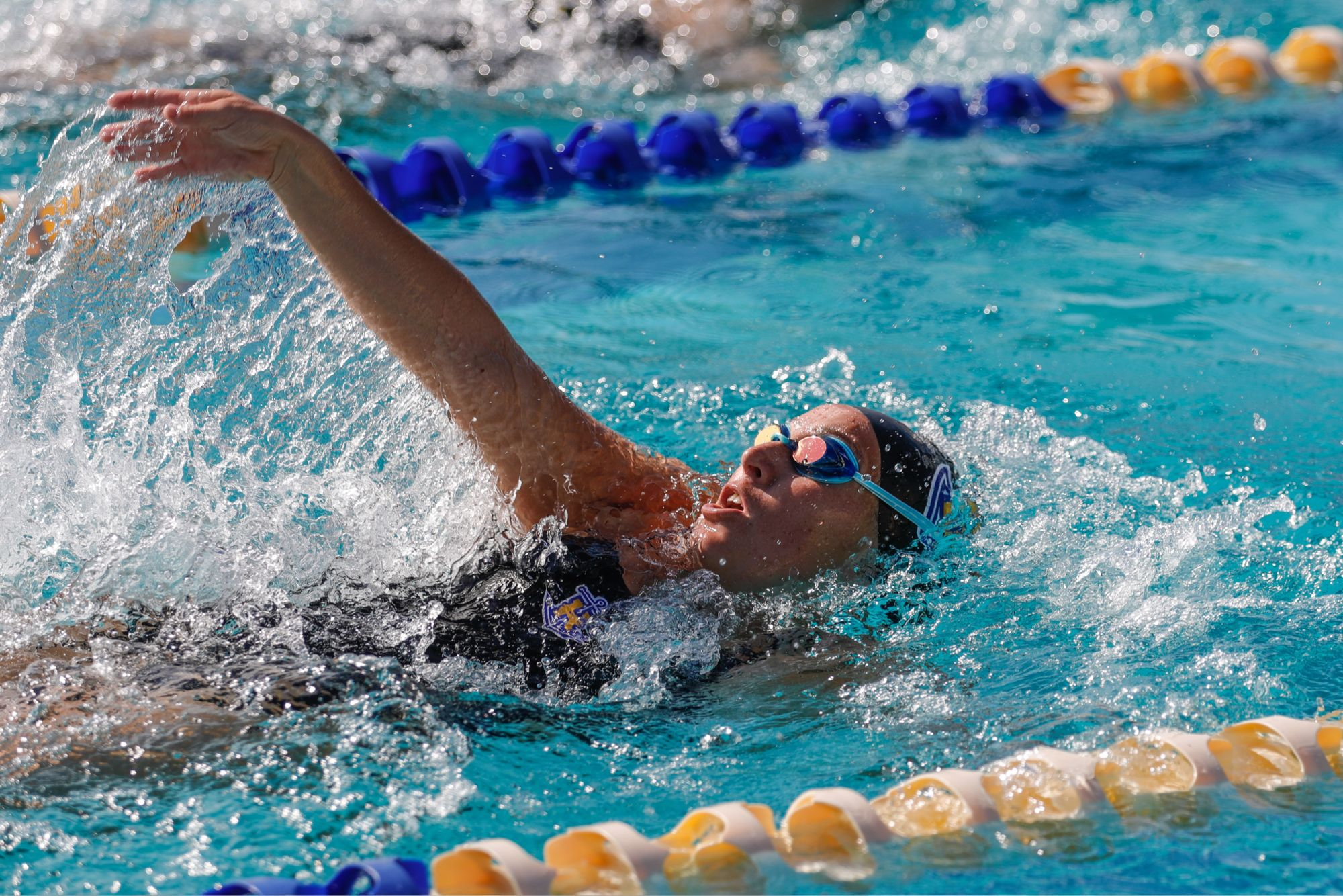 A swimmer in the pool during a meet doing the backstroke.