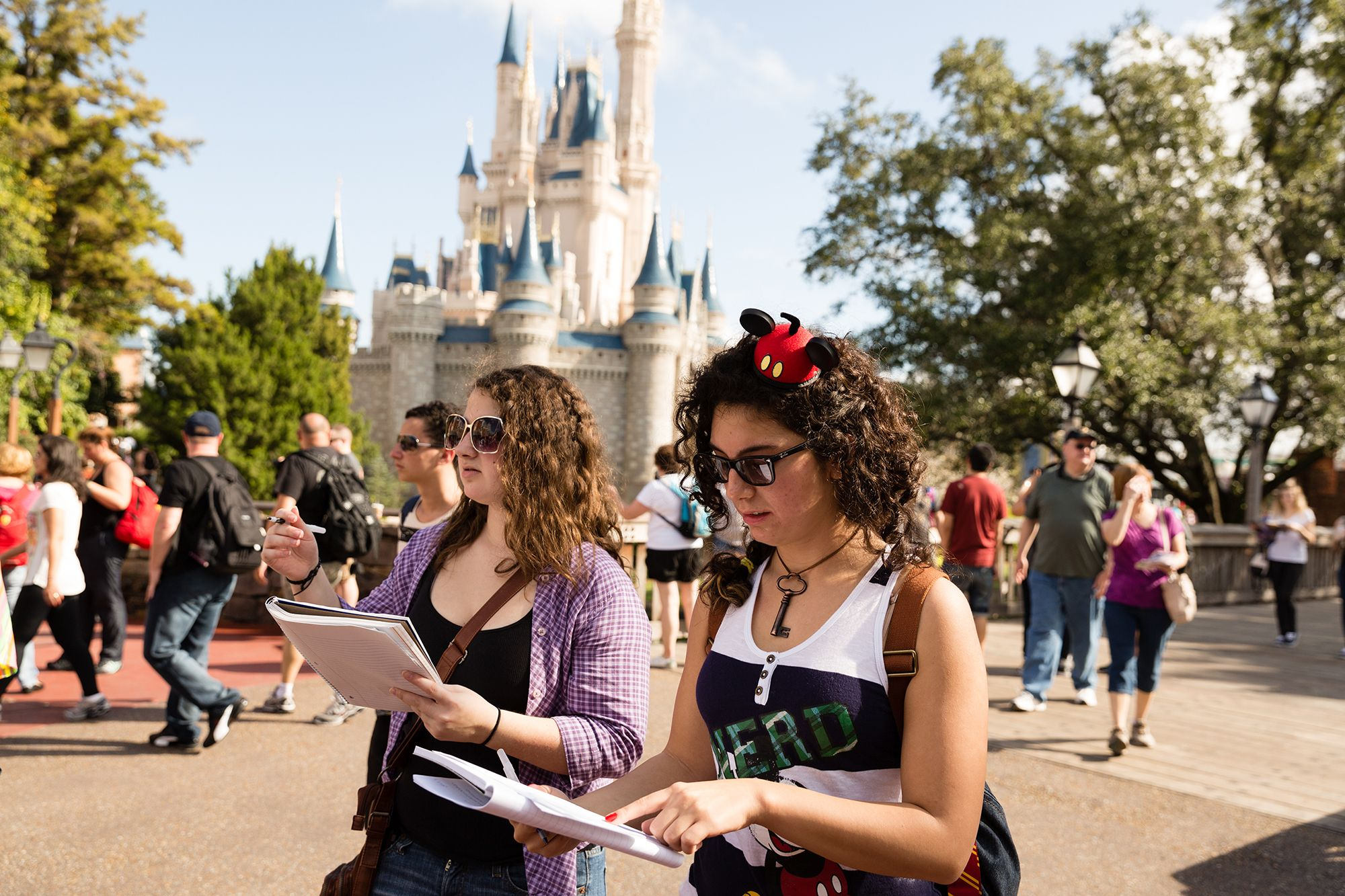 Two students do a class project at the Magic Kingdom in Disney World.